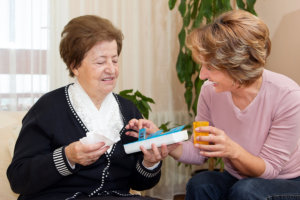 caregiver giving a medications to her patient