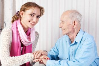 caregiver holding her patient's hands