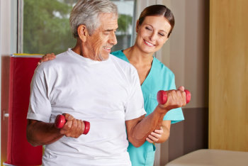 caregiver assisting his patient in exercising