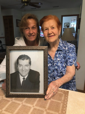 smiling caregiver and old lady with a picture frame of her husband